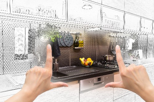 A person holds up their hands over a colored in section of a kitchen design sketch done by a professional kitchen design company.